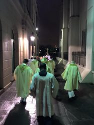 The clergy who will celebrate midnight mass, walk down Pere Antoine Alley.