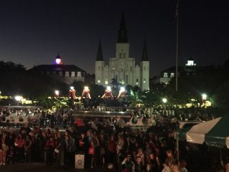 Jackson Square lit up with the Cathedral in the background and the Cabildo lit up in the colors of the French national flag